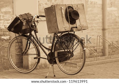 Shabby black hat and suitcases on the bike. Retro-styled and sepia toned image - stock photo