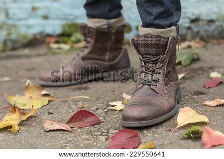 shabby brown leather boots against autumn background - stock photo