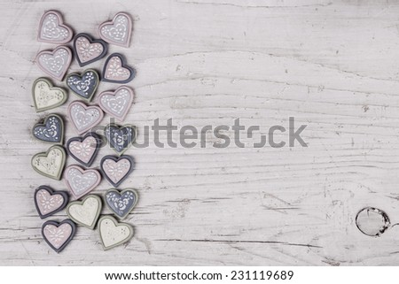 Shabby chic grey wooden background with a collection of hearts on the frame. - stock photo