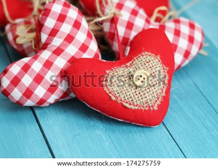Shabby chic valentine hearts , red and white gingham cotton rustic hearts, with buttons , hessian and straw on blue wooden boards  - stock photo