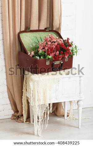 Shabby chic wedding. Wedding floral decor composition, flowers in vintage brown suitcase at bedside. Old suitcase with bouquet roses. Vintage, rustic, country decor. Floristic decoration. Flowerbed.  - stock photo