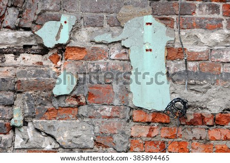 Shabby grungy red brick wall with some green plastering left - stock photo