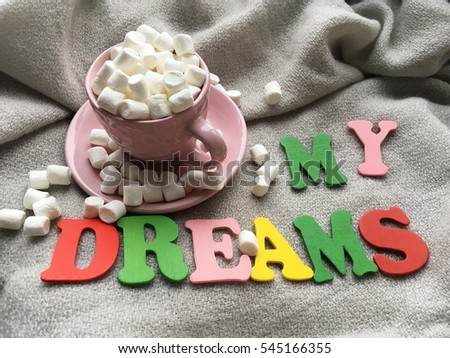 Shabby pink cup with marshmellows. Dreams wooden letters on grey blanket.
