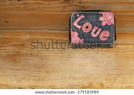 Shabby torn denim blue purse with embroidered pink word LOVE and flowers on rustic wooden background, the focus is not centered,  on the word  LOVE - stock photo