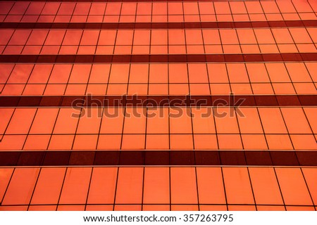 Shade of orange glass windows of modern office building and sky reflection for texture and background - stock photo