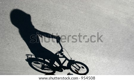 shade on the road of a child on  a bicycle