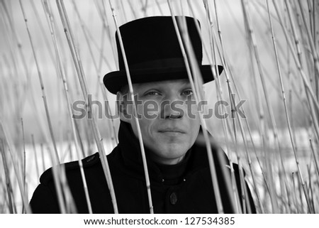 Shaded man looking through reed brush at winter