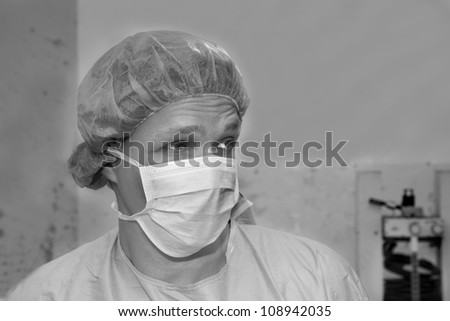 Shaded surgeon making some thoughts about coming surgery - stock photo