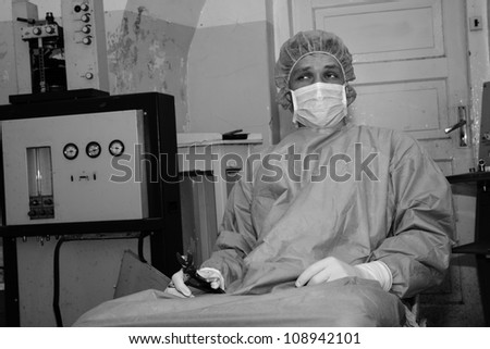 Shaded surgeon take tool before coming difficult surgery - stock photo