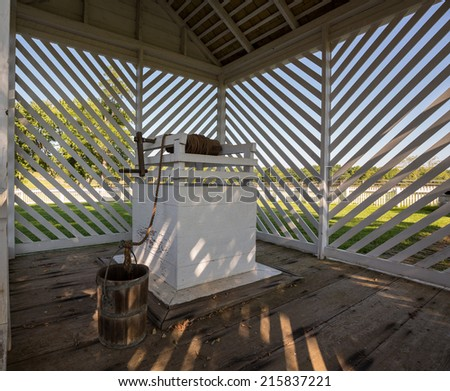Shaded water well and wooden bucket at McLean House in Appomattox national park - stock photo