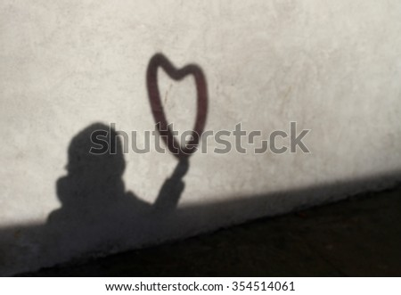 shadow and silhouette of a child bringing a heart balloon in the hand - stock photo