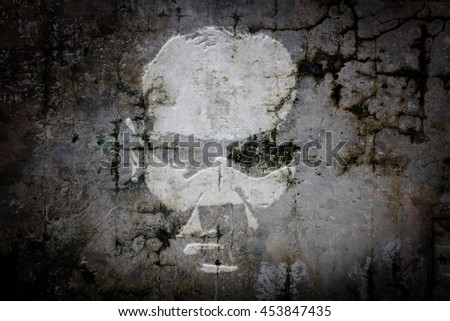 Shadow apparition of an eerie man face on a grungy concrete wall.