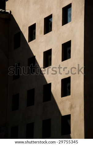 Shadow Bisects Brown Building with Rectangular Windows