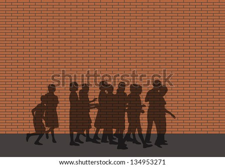 shadow of a group of children walking along an impassable red brick wall - stock photo