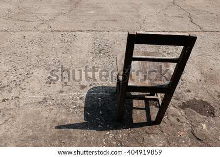 Shadow of a single chair on the cement floor in the afternoon