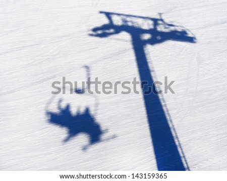shadow of a skier on a skilift - stock photo