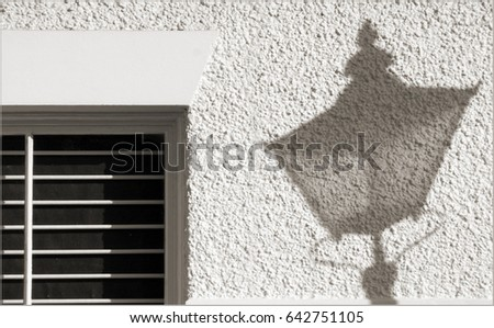 Shadow of a street lamp cast onto the side of a building with a shuttered window