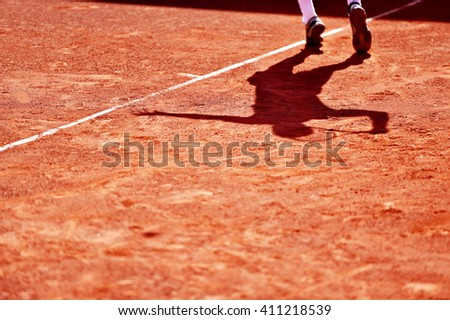 Shadow of a tennis player in action on a clay court - stock photo