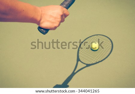 shadow of a tennis player in action on a tennis court - stock photo