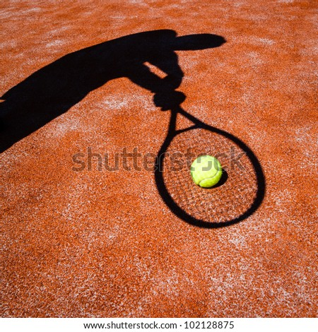 shadow of a tennis player in action on a tennis court (conceptual image with a tennis ball lying on the court and the shadow of the player positioned in a way he seems to be playing it)