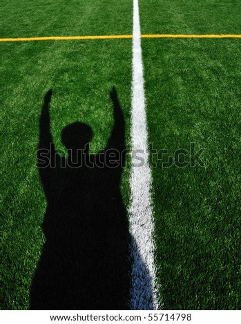 Shadow of American Football Referee Signaling a Touchdown - stock photo