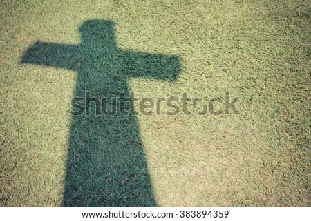 Shadow of Christian cross on green grass floor with Vintage filter style 2 - stock photo