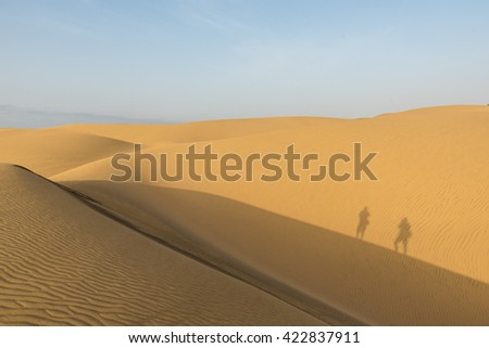 Shadow of Couple in sand dunes in desert of gran canaria, spain