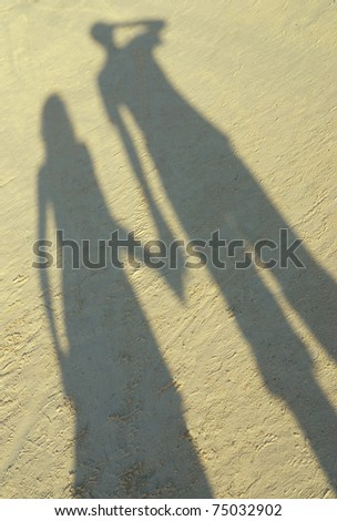 Shadow of couple on beach - stock photo