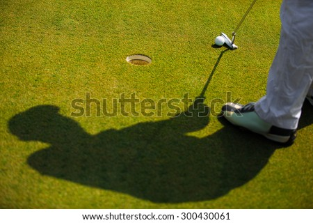 Shadow of golfer That is going to putt a golf ball - stock photo