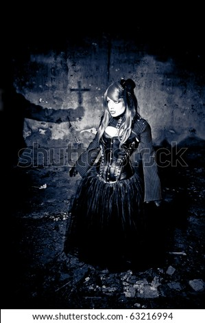 Shadow of hand holding crucifix in front of possessed woman - stock photo