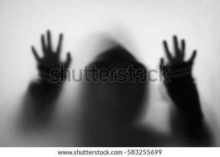 Shadow of horror man in jacket with hood.Hands on the glass.Dangerous man behind the frosted glass.Mystery man.Halloween background.Black and white picture.Blur picture
