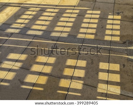 Shadow of pergola roof on the the pavement - stock photo