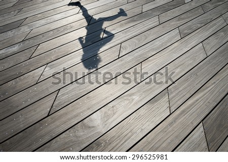 Shadow of runner jogging across weathered smooth wood plank boardwalk background textured with modern angular lines - stock photo
