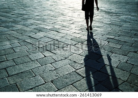Shadow of single man with cigarette in right hand walking on cobbled street. - stock photo