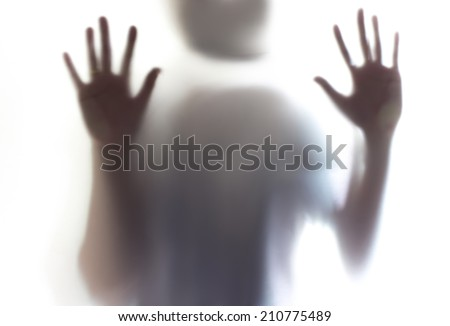 Shadow of woman standing behind door frosted glass - stock photo