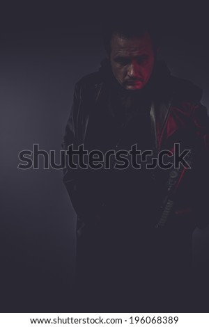 shadow portrait of stylish man with long leather jacket, gun armed - stock photo