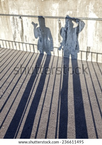 Shadows of a couple photographers with cameras. - stock photo