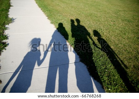 Shadows of a family of five walking in the park holding hands - stock photo