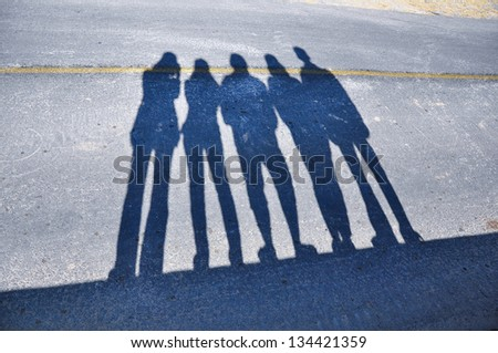 Shadows of people on street - stock photo