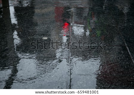 Shadows of people reflected in a rainy floor