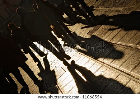 Shadows of people walking in a street of the city. The afternoon sun gives a warm and dramatic light. - stock photo