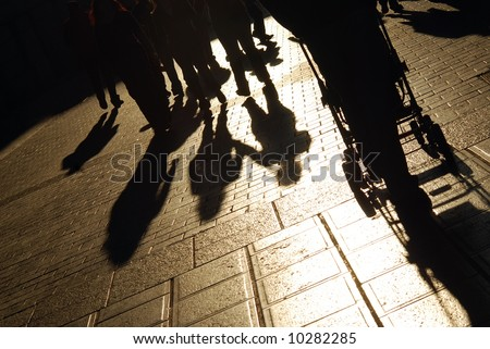 Shadows of people walking on the city street - stock photo