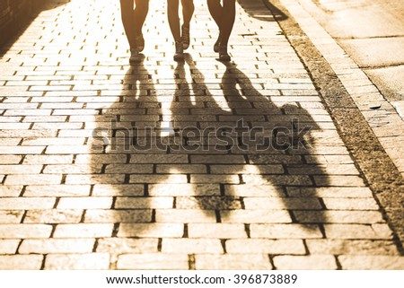 Shadows of three girls walking on a sidewalk in the city at sunset. Focus on the shadows, and harsh backlight with flares. Lifestyle concept with a different point of view. - stock photo