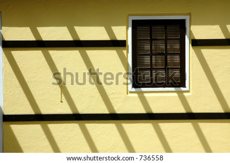 shadows on yellow wall with window - stock photo
