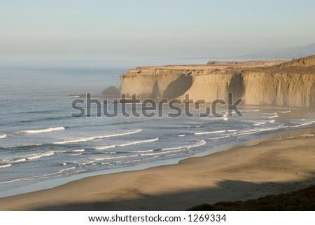 Shadows retreat across beach as sun rises over Tunitas Creek Beach in rural San Mateo county, California. - stock photo