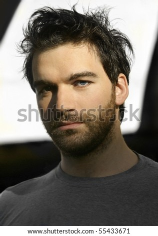 Shadowy portrait of a young bearded man - stock photo