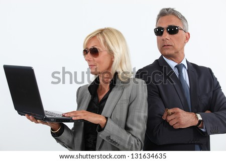 Shady mature business couple with a laptop - stock photo