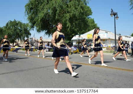 SHAFTER, CA - MAY 4: Flag waving high school girls march behind the band during the Cinco de Mayo Festival parade on May 4, 2013, at Shafter, California.