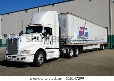 SHAFTER, CA - SEPTEMBER 17, 2015: This large industrial warehouse complex is a transportation hub for Central California. A tractor trailer rig unloads its cargo at the loading dock. - stock photo