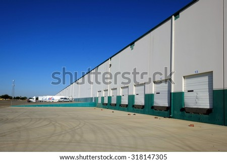 SHAFTER, CA - SEPTEMBER 17, 2015: This large industrial warehouse complex is a transportation hub for Central California. Tractor trailer rigs are ready at the loading docks. - stock photo